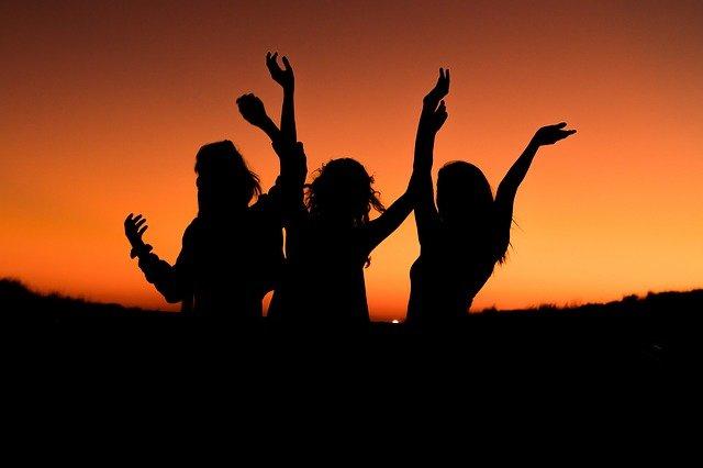踊っている女性三人のシルエット